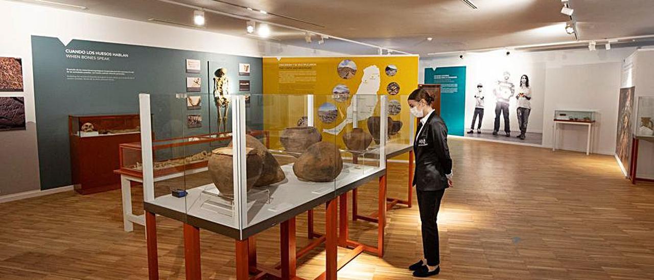 Una joven observa diversas piezas del Museo Arqueologico insular.