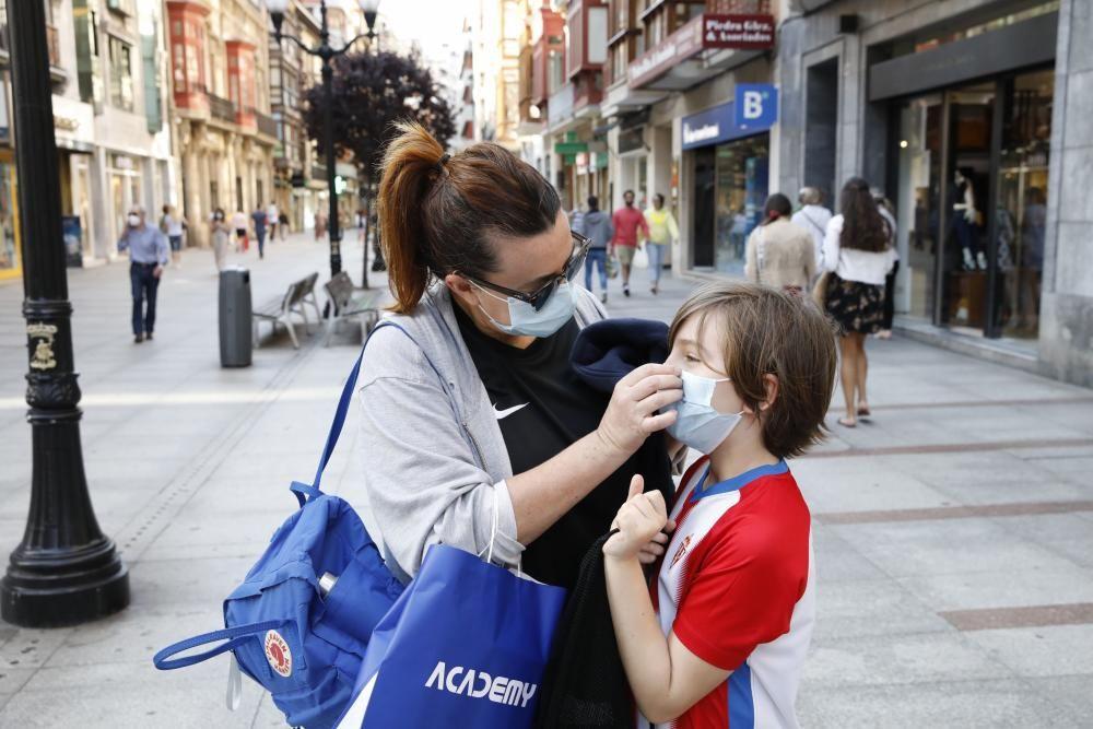 Gente con mascarilla y sin ella por el centro de Gijón.