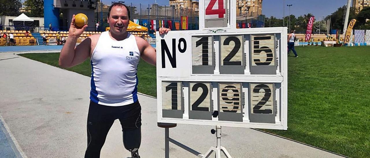 David Fernández, ayer en Sevilla, con el peso que lanzó, junto a la marca de su nuevo récord de España. |