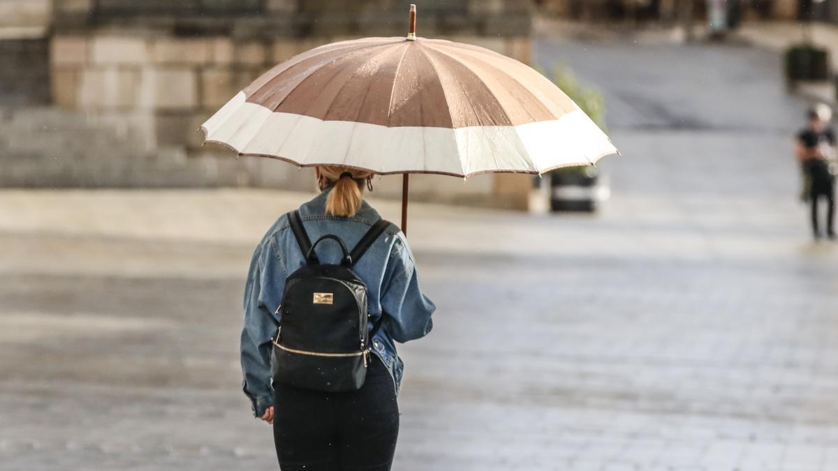 Una mujer lleva un paraguas durante la tormenta de este martes en Cáceres