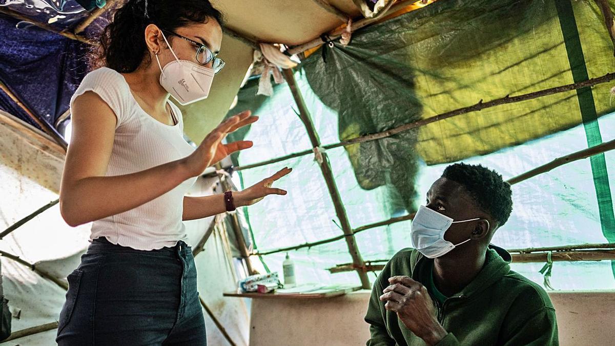 Sandra atiende a un grupo de migrantes frente al campamento de Las Raíces.