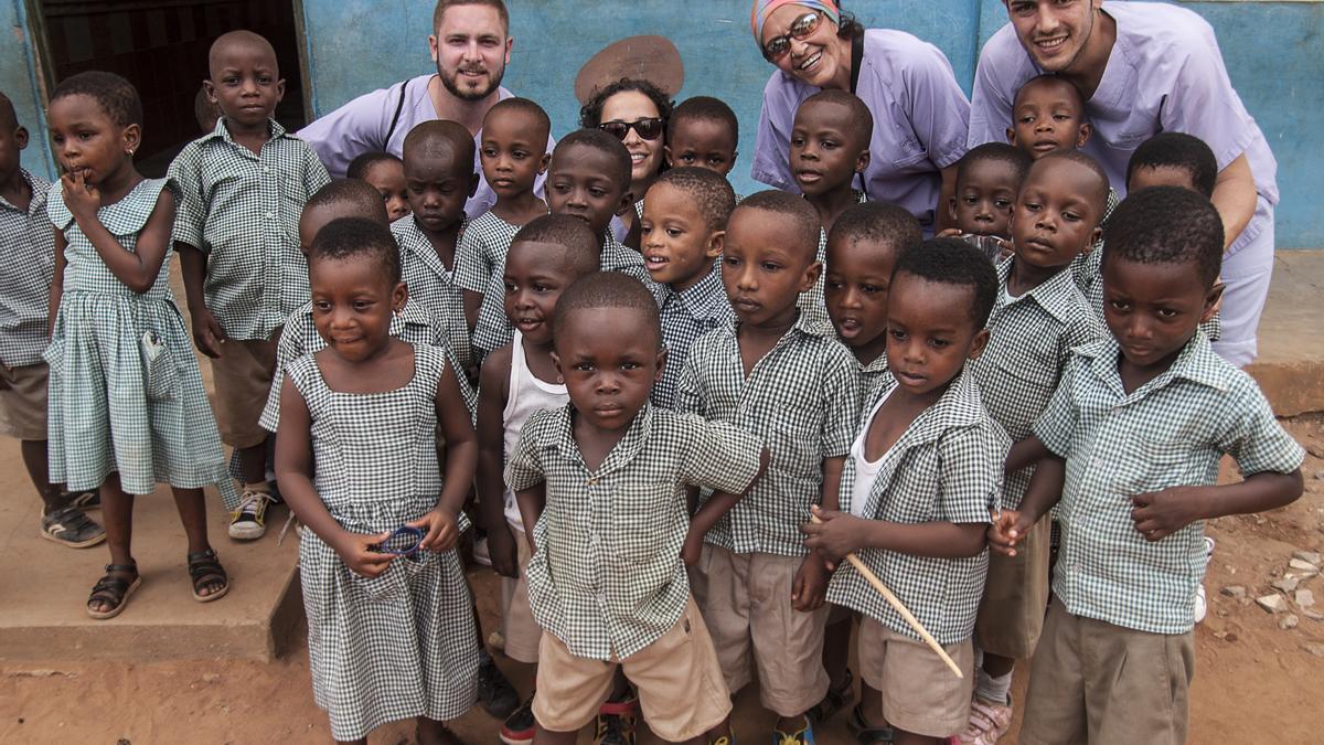 Miembros de la oenegé con niños que se benefician de su labor solidaria.