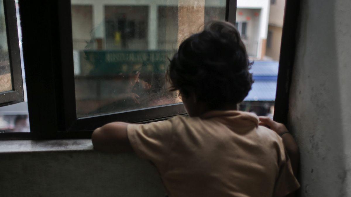 Un niño, de espaldas, mira por la ventana.