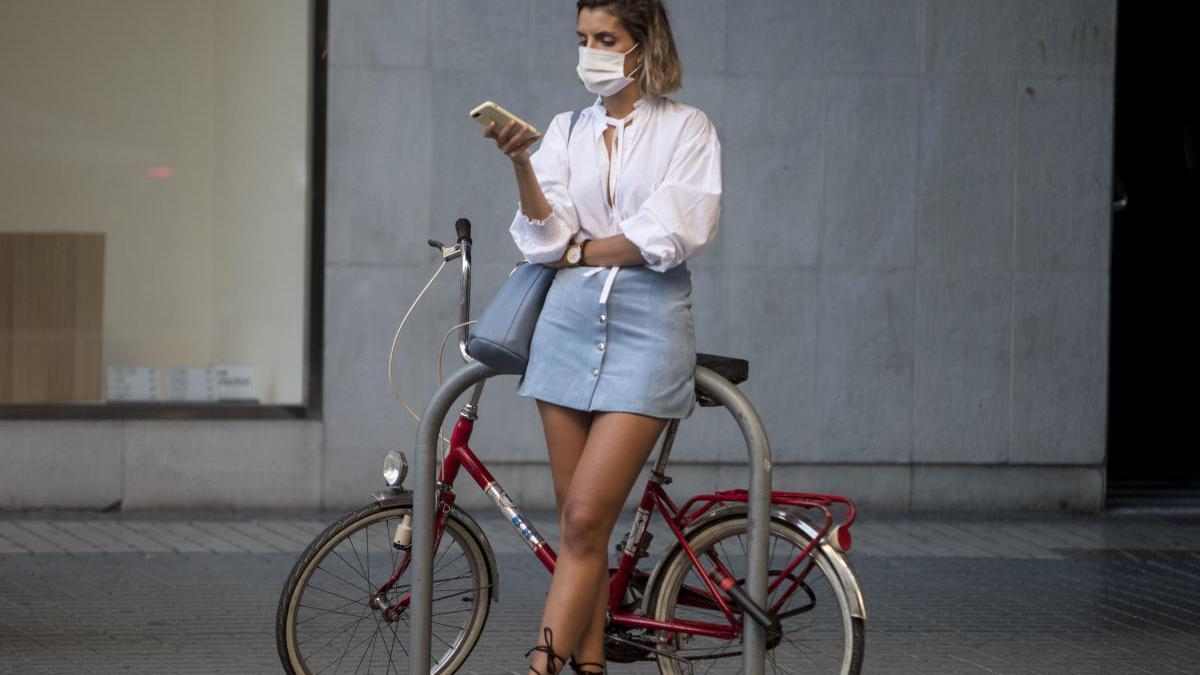 Una joven mira su móvil protegida con una mascarilla en el centro de València.