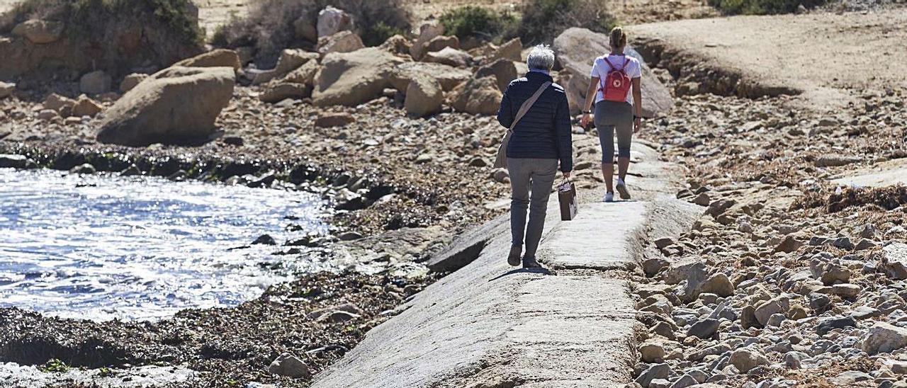 Usuarios de la playa de San Juan caminan por encima del colector hacia Cabo de las Huertas.