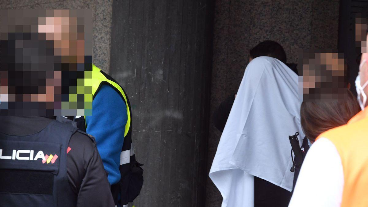 El detenido, cubierto con una sábana, sale del edificio de Ronda de Nelle donde ocurrieron los hechos.