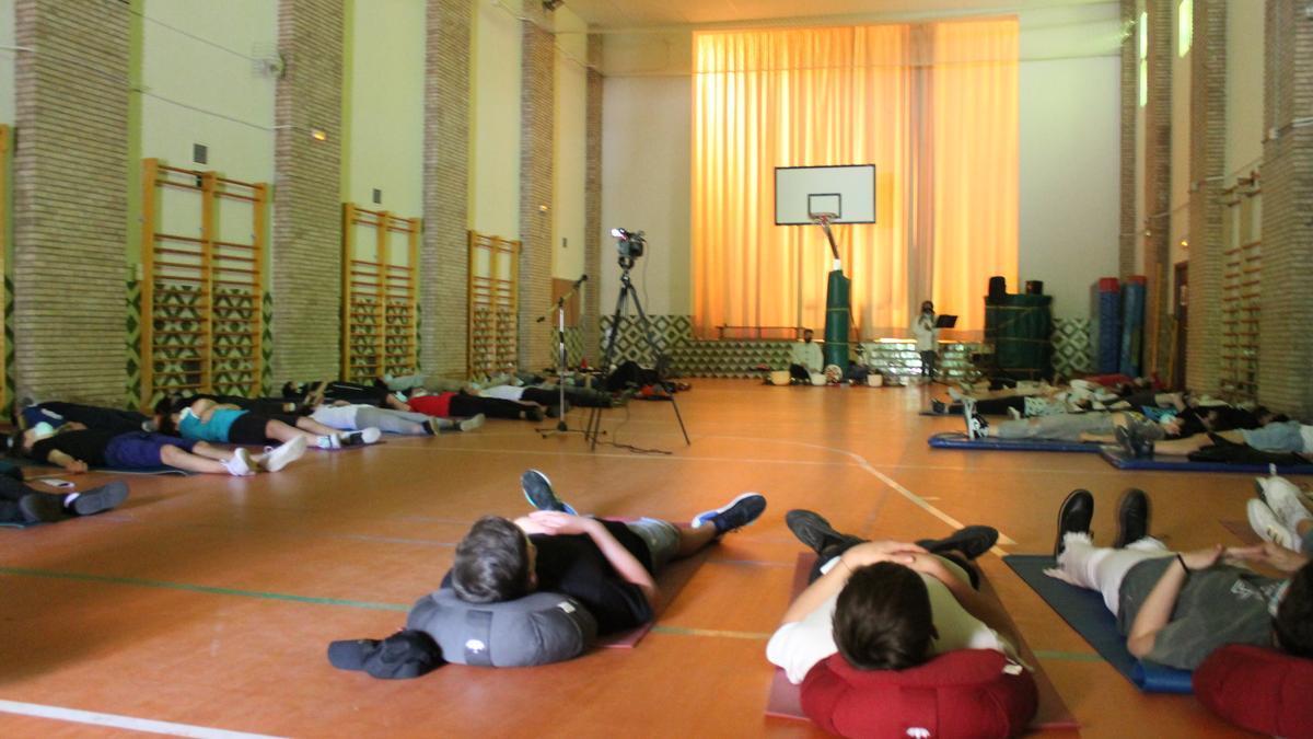 Los alumnos realizan ejercicios de mindfulness en el pabellón con la música del grupo Re-sonando.