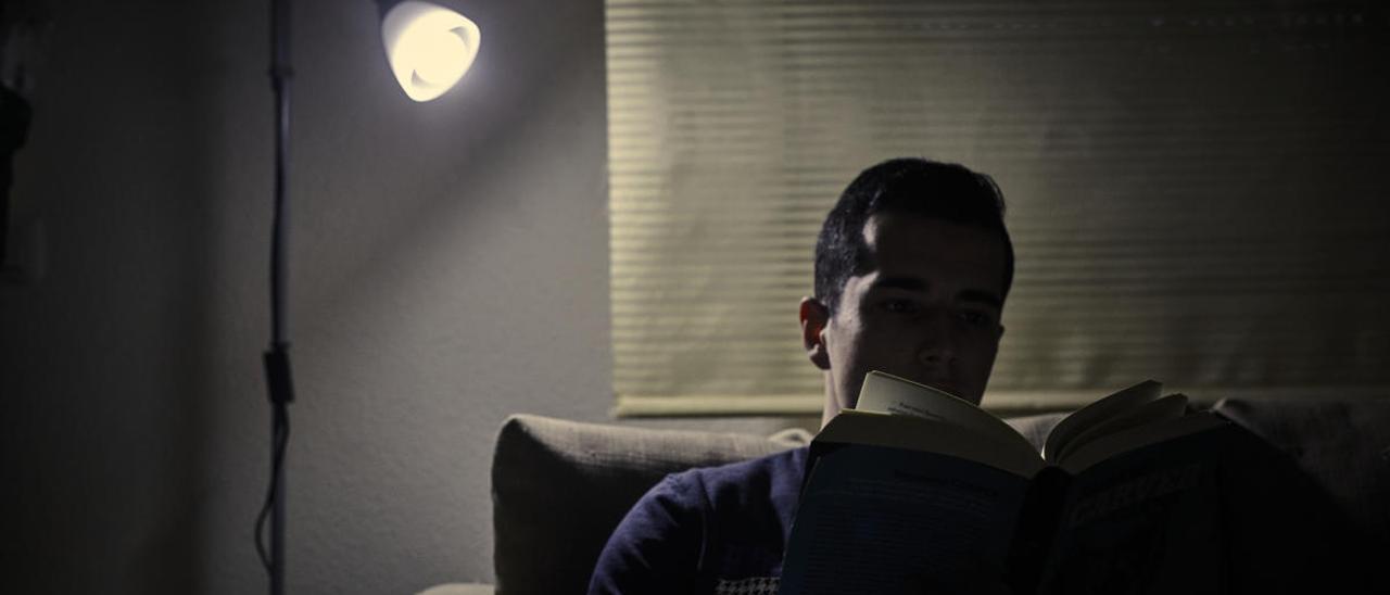 Un hombre lee bajo la luz de una bombilla