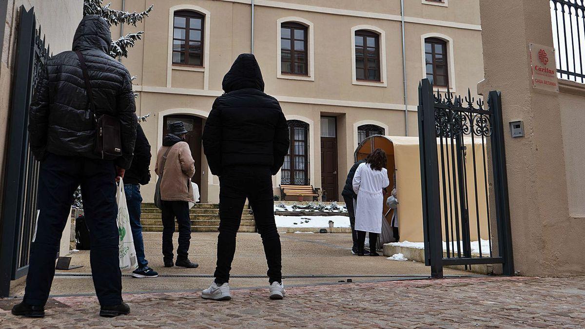 Ciudadanos aguardan su turno en la cola para recoger comida caliente en la Casa Betania.