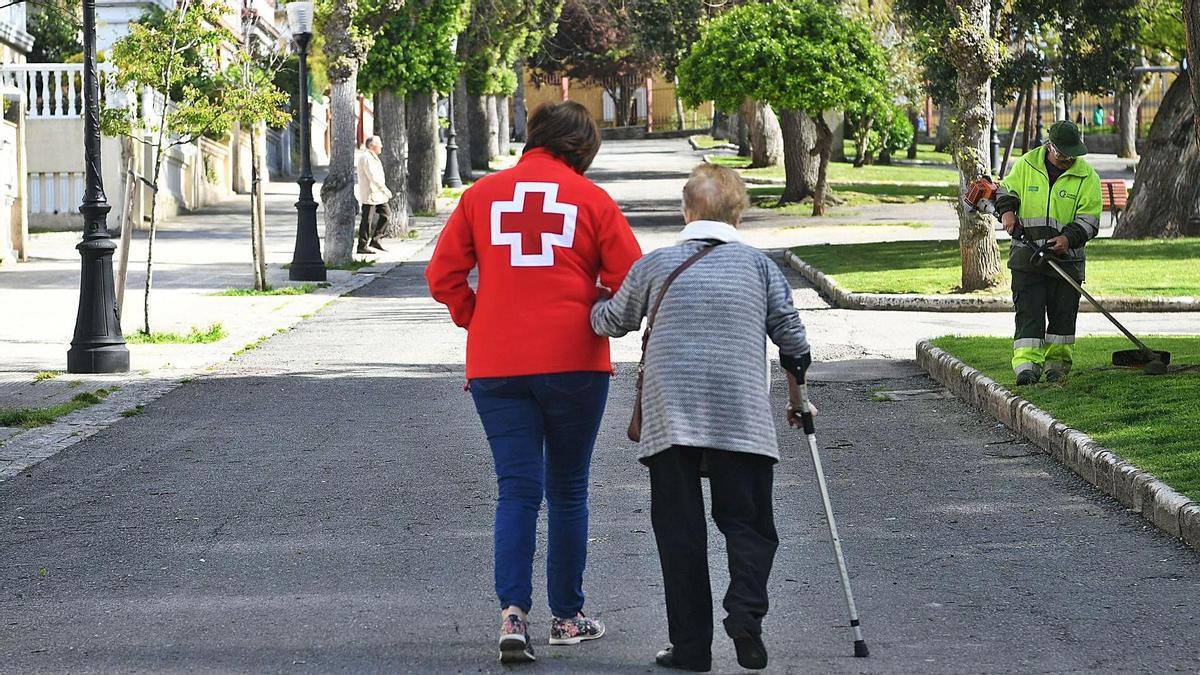 Una voluntaria de Cruz Roja acompaña a una mujer en A Coruña.   | // CARLOS PARDELLAS