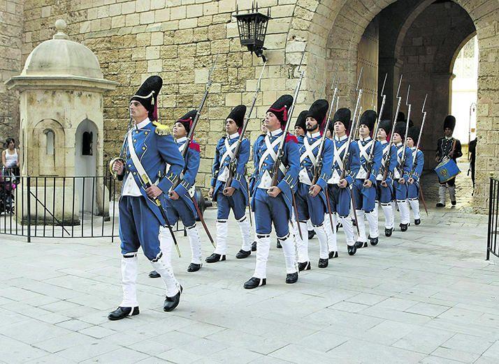 Soldados vestidos de época desfilan en el cambio de guardia de la Almudaina.