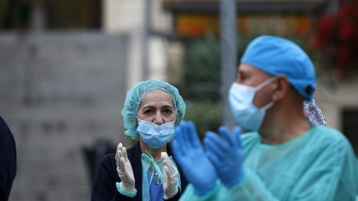 Dos sanitarios, durante el aplauso en en las pertas del Hospital Regional.