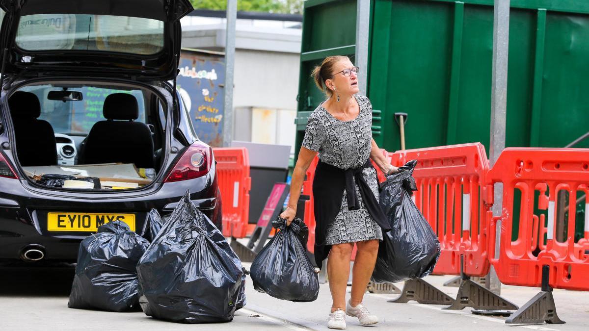 Una mujer reciclando.