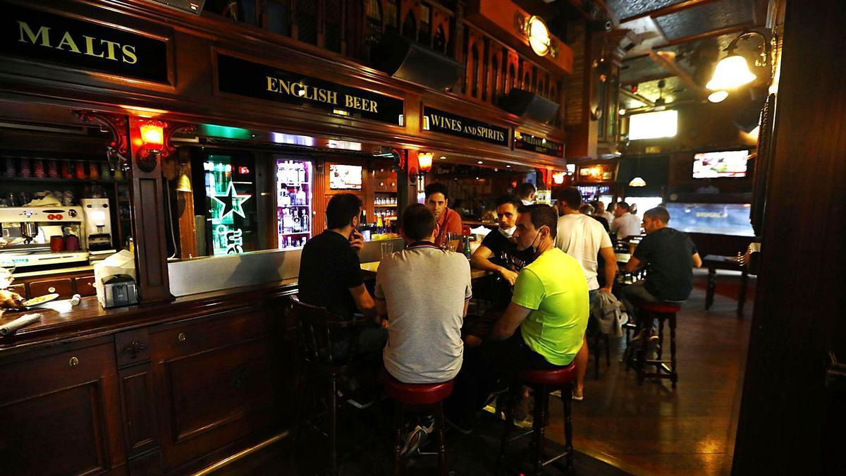 Un grupo de jóvenes sentados en una mesa en un pub, a medidados de junio. El consumo en barra continúa prohibido. | JAIME GALINDO / ARCHIVO