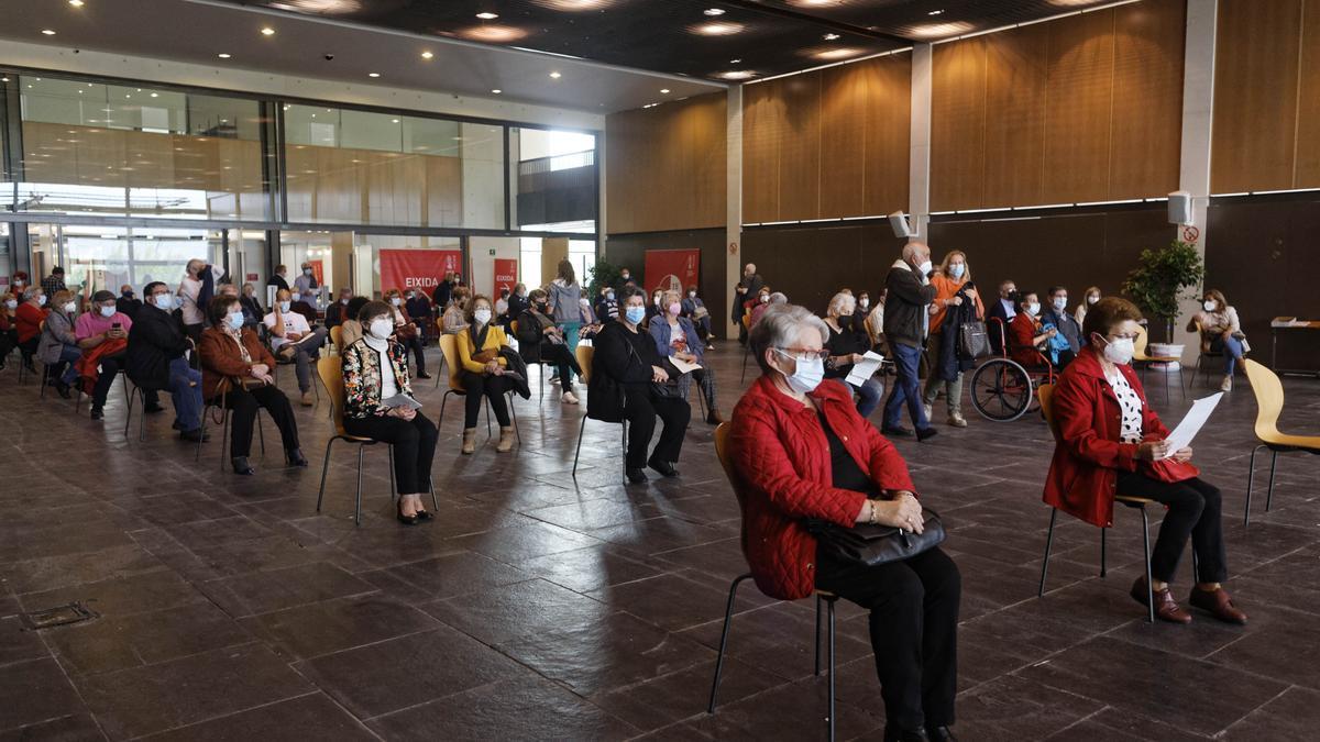 Un grupo de personas espera en la sala habilitada en el Auditori de Castelló tras haber recibido una dosis de la vacuna de Pfizer durante la tarde de este lunes.