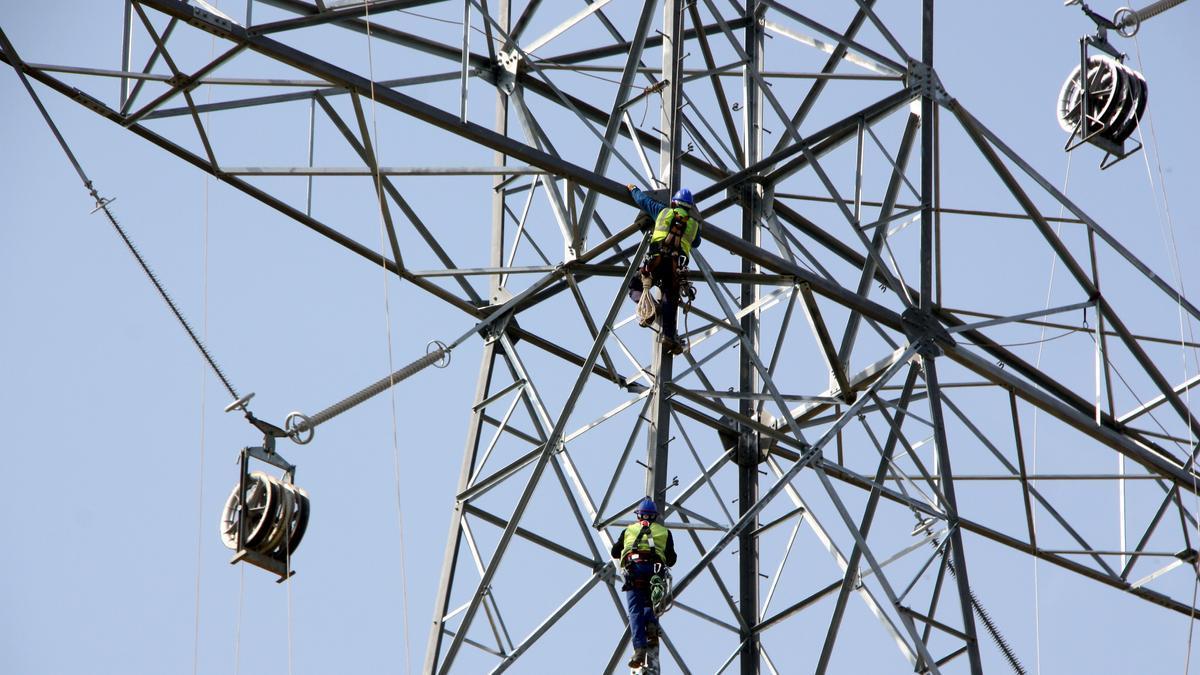 Un operari treballa en una torre elèctrica