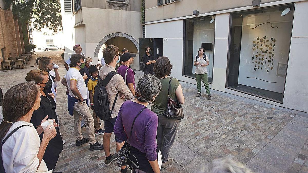 Visitants al Pou Rodó de Girona, escoltant les explicacions d'un dels artistes participants. | MARC MARTÍ