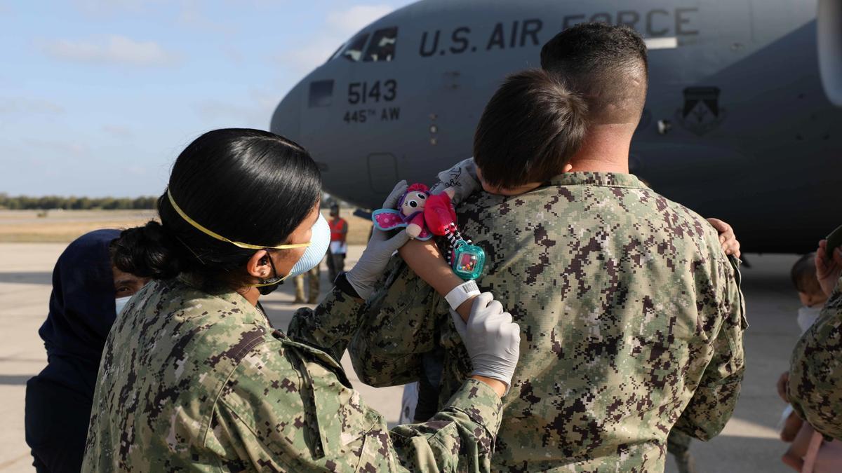 Dos soldados estadounidenses atienden a un niño recién llegado desde Kabul.