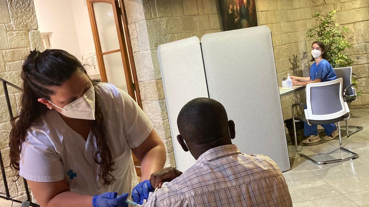 Pla mitjà d'un home en situació de vulnerabilitat rebent la vacuna aquest divendres al Convent de Santa Clara de Manresa. Imatge de l'11 de juny del 2021. (Horitzontal)