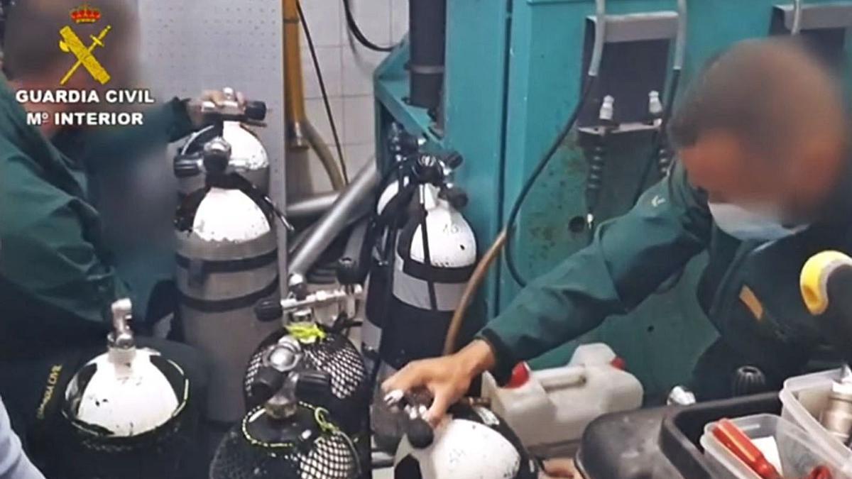 Los investigadores revisan las botellas de oxígeno del centro de buceo.