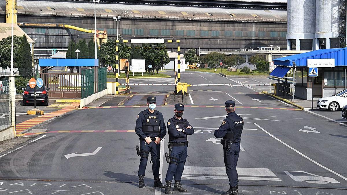 Agentes de la Policía Nacional, en la entrada de Alu Ibérica A Coruña, el pasado jueves. |   // VÍCTOR ECHAVE