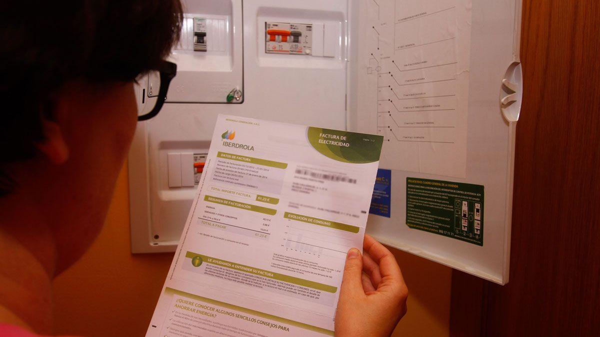 Una mujer comprueba una factura eléctrica, junto al contador.