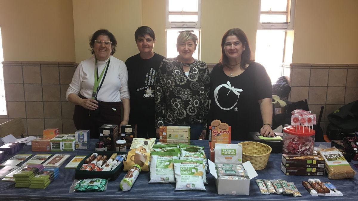 Cuatro de las más de cien personas voluntarias con las que Proyde cuenta en Zaragoza, en una venta de productos de comercio justo.