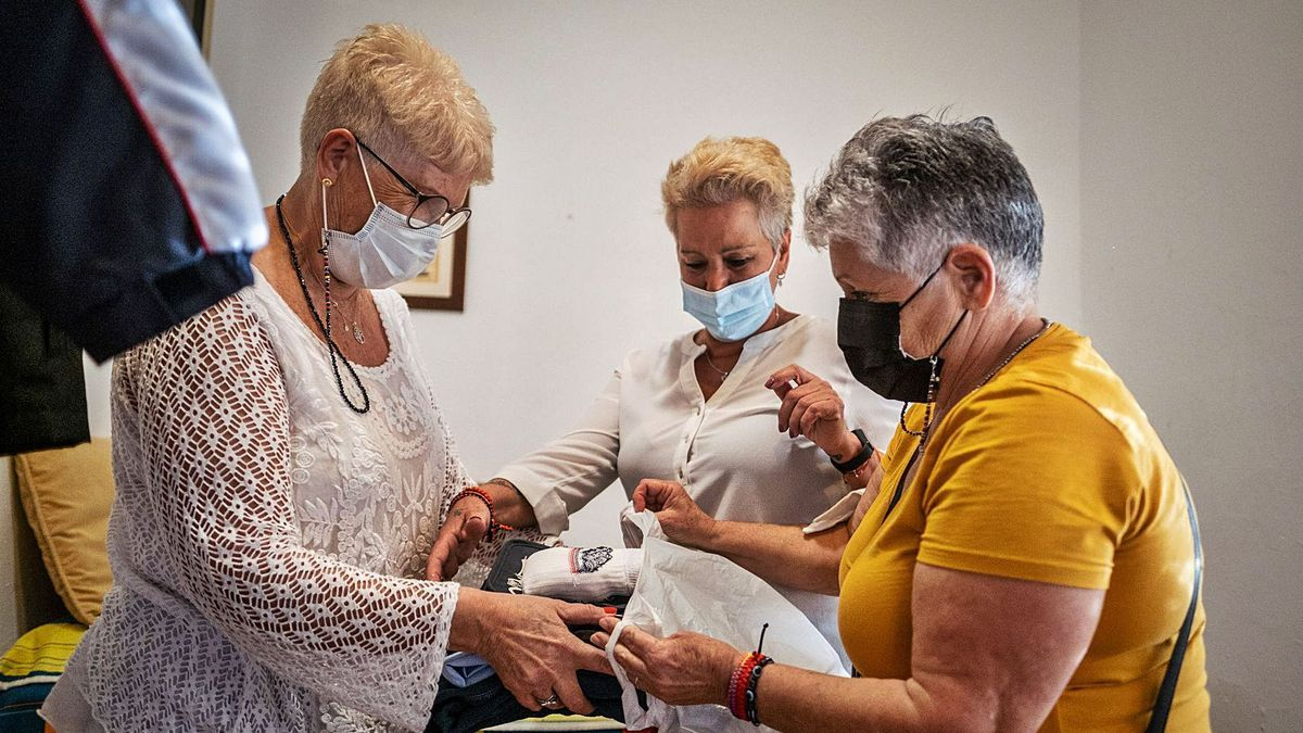 Candelaria, Miguelina y Conchi González preparan una entrega de ropa.