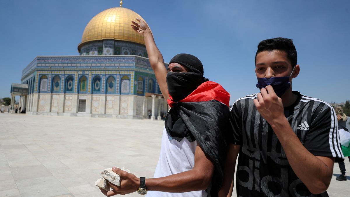 Un manifestante palestino gesticula mientras sostiene piedras cerca de la Cúpula de la Roca durante los enfrentamientos con las fuerzas de seguridad israelíes en el recinto que alberga la mezquita de Al-Aqsa