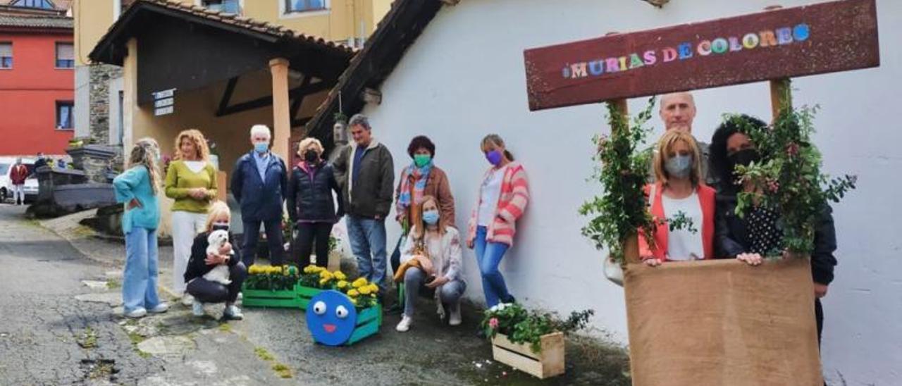 """La concejala de Turismo y la presidenta de """"La Colegiata de Murias"""", con vecinos, en Murias."""