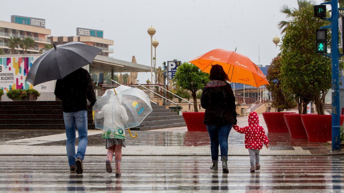 Una familia camina protegida de la lluvia ayer en Alicante