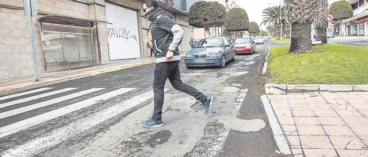 Un peatón cruza la avenida Juan de Bethencourt cuyo estado critican vecinos y conductores.