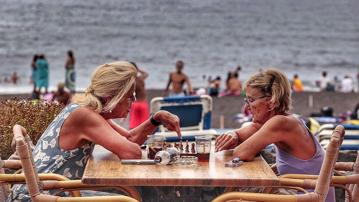 Dos turistas juegan al ajedrez en una terraza de Playa Jardín, en Puerto de la Cruz.