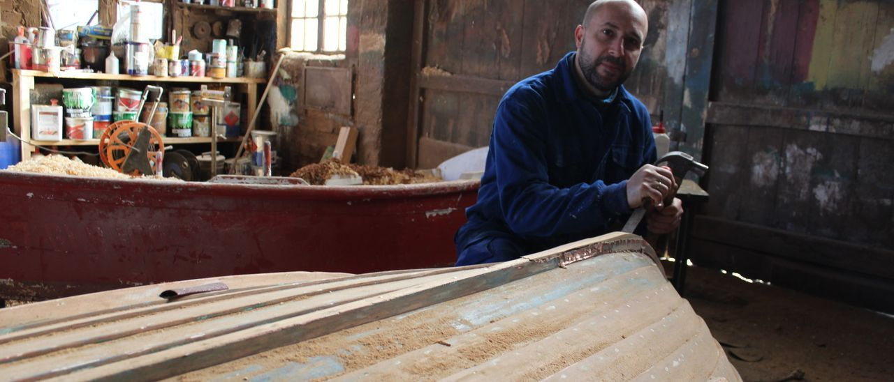 El carpintero Martín González, reparando una lancha en su taller.
