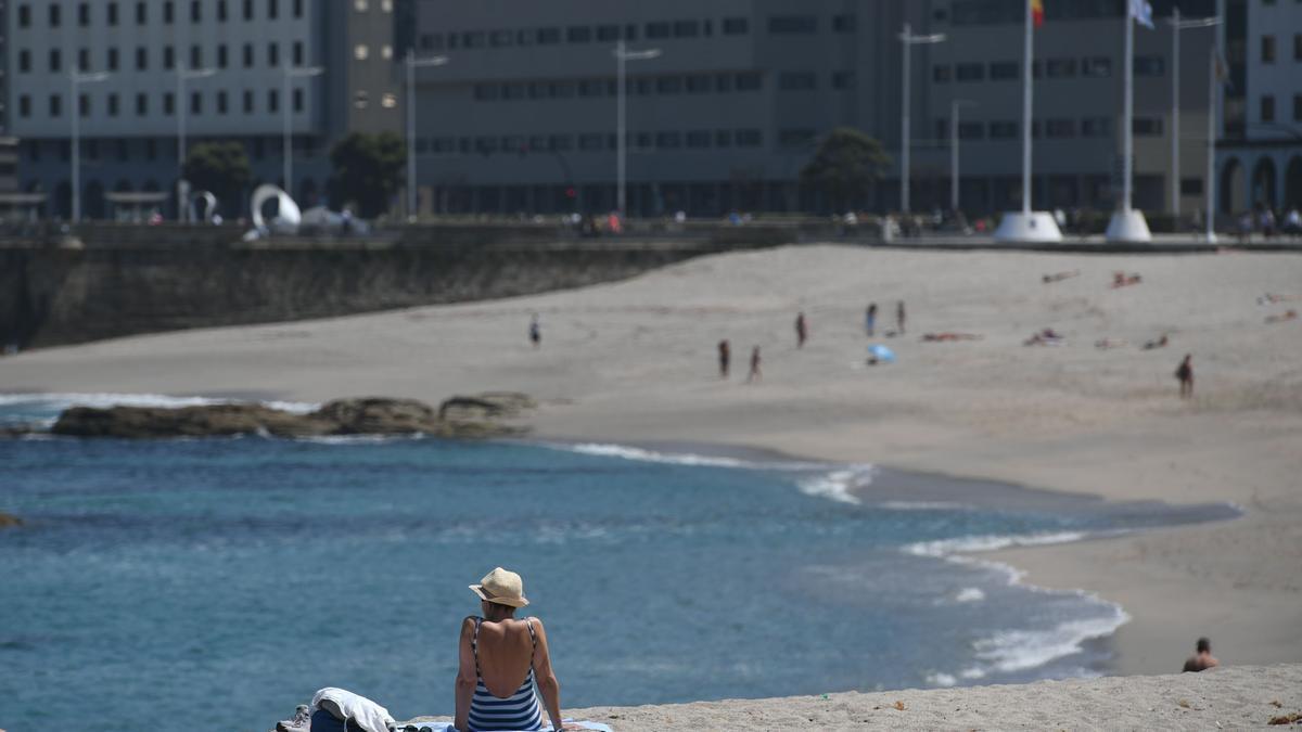Bañistas al sol en la playa coruñesa de Riazor.