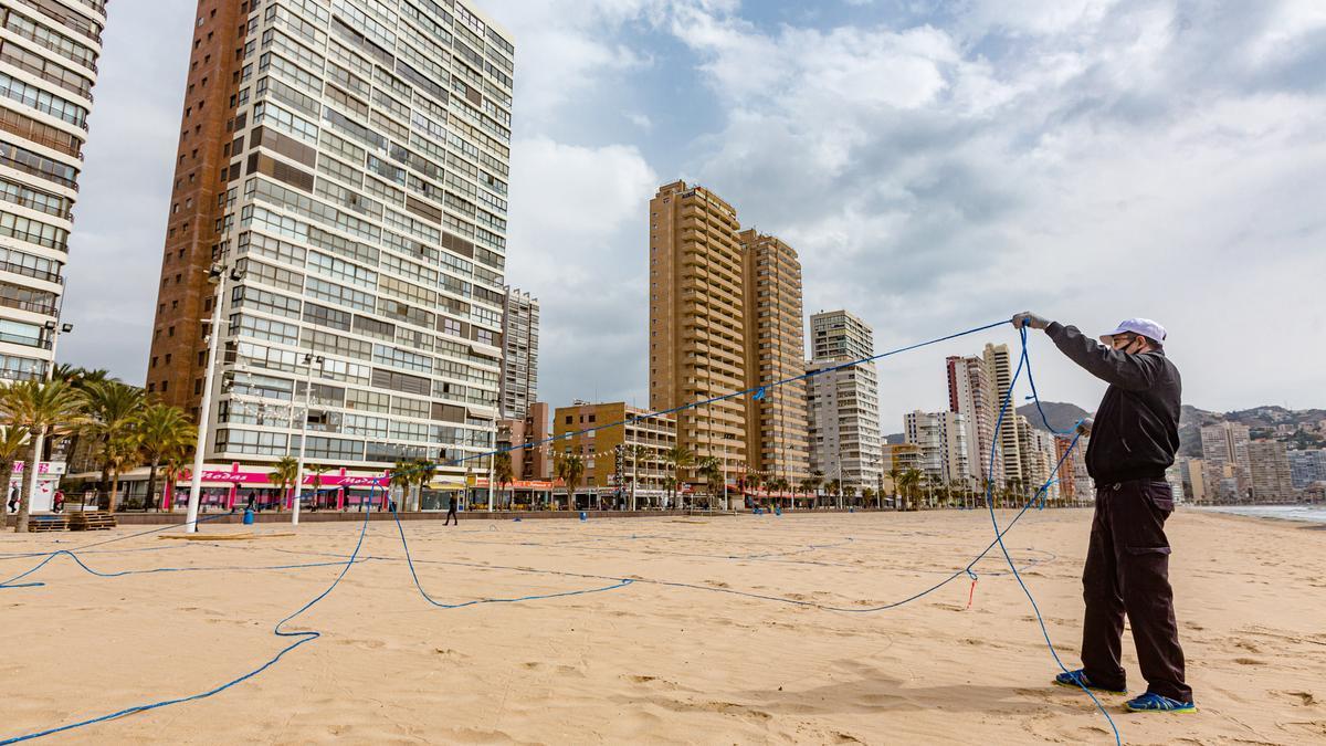 Operarios colocan las redes de las parcelas de la playa de Benidorm este lunes.