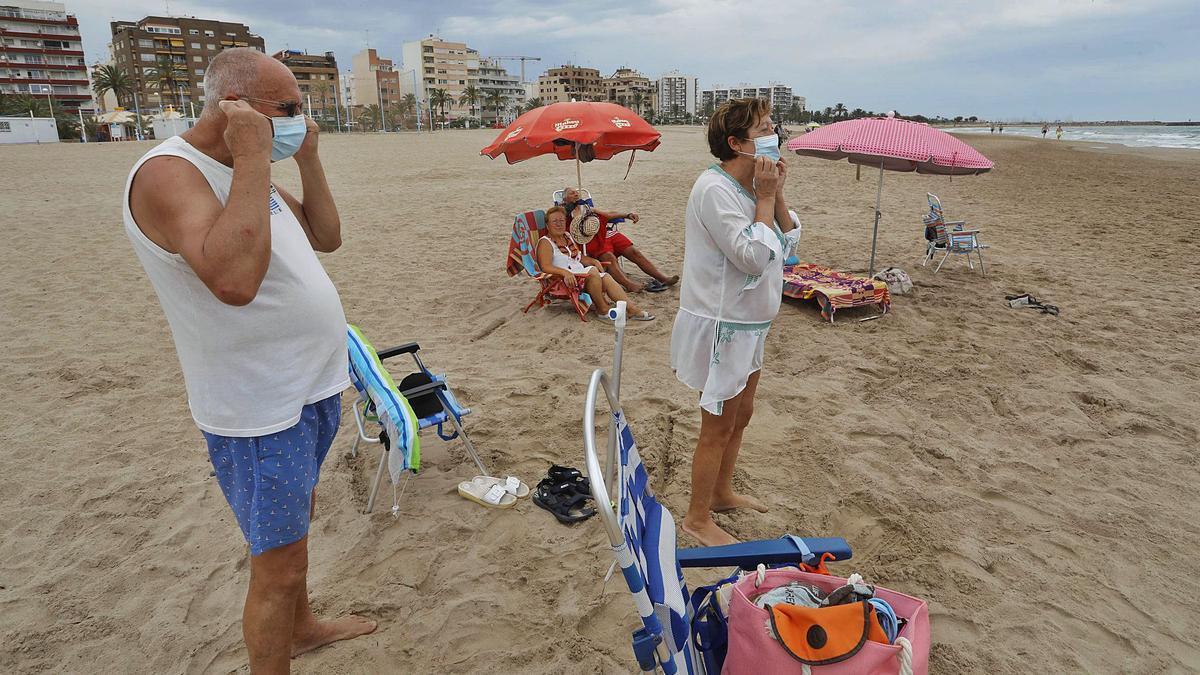 Un grupo de personas acude ayer a la playa del Port de Sagunt con la mascarilla puesta, tal y como recoge la normativa estatal y autonómica contra la covid-19.    DANIEL TORTAJADA