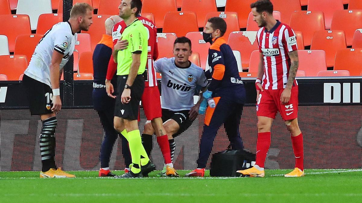 Hugo Guillamón se incorpora con la ayuda del cuerpo médico y los fisios tras caer lesionado frente al Atlético. | F. CALABUIG