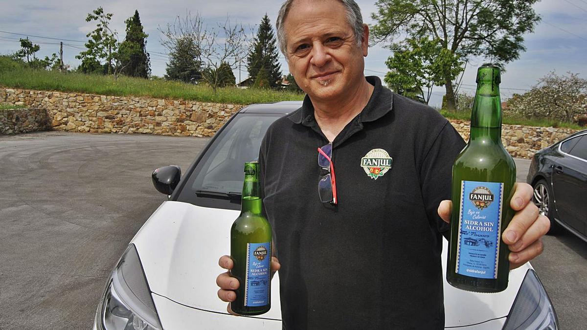 Carlos González, mostrando dos botellas de sidra sin alcohol, en su domicilio de Hevia, en Siero. | A. I.