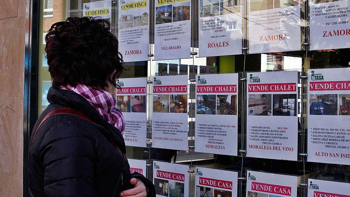Una mujer observa la oferta de una inmobiliaria.   LOZ