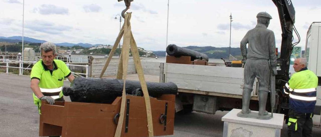 Operarios municipales, instalando ayer en el muelle de Figueras las dos piezas restauradas.