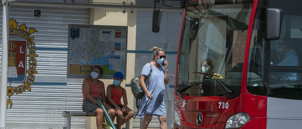 Una pasajera protegida con la mascarrilla sube a un autobús urbano en Alicante.