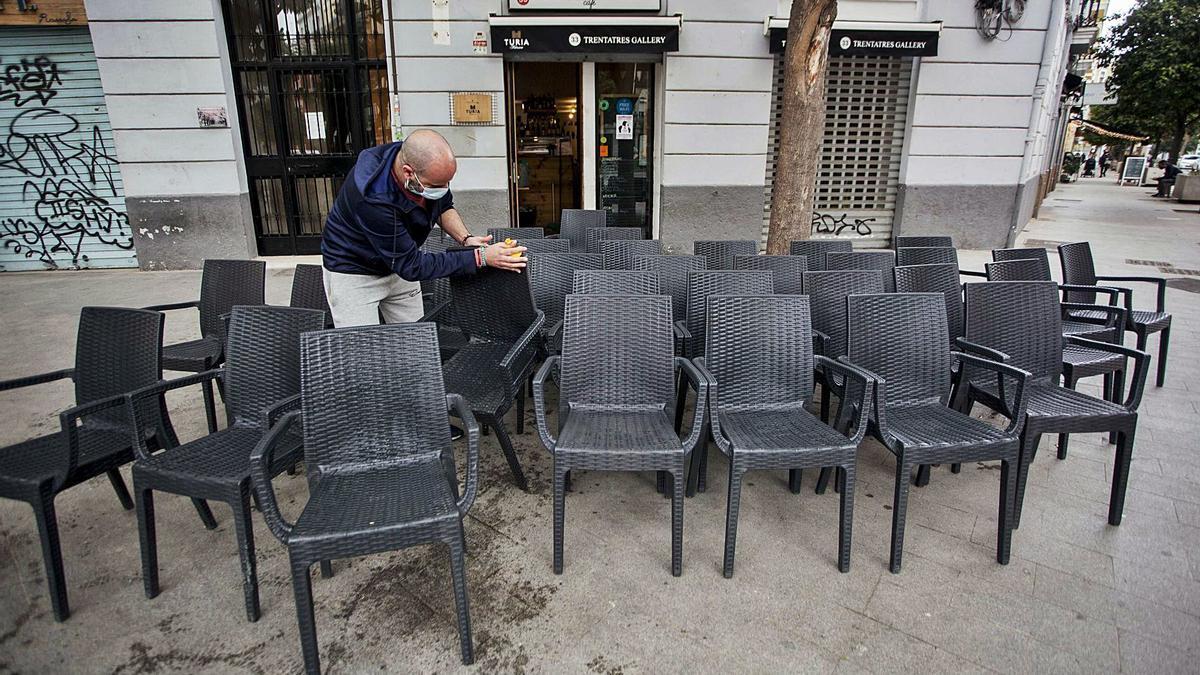 El propietario de un bar de Russafa limpia las sillas de su terraza horas antes de la comparecencia de ayer de Ximo Puig. | F. BUSTAMANTE