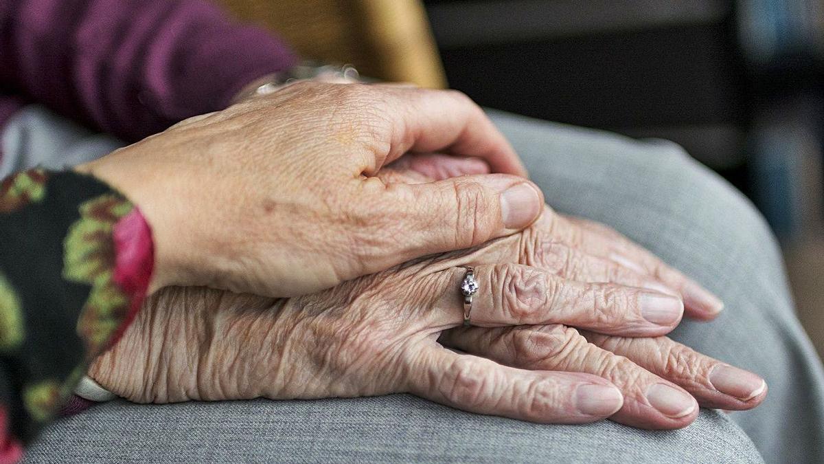 Una mujer pone su mano sobre las de una persona mayor.   | // L.O.