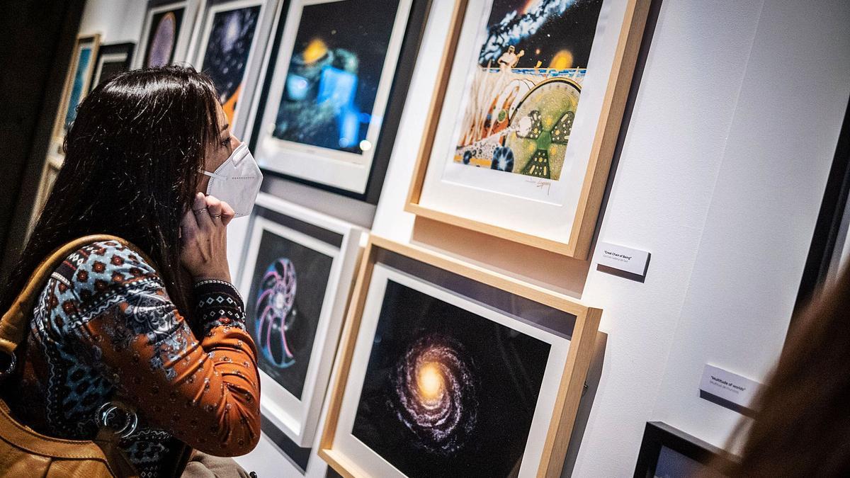 Una mujer contempla algunas de las obras de Jom Lomberg, director artístico de la serie Cosmos y fiel amigo de Carl Sagan     ANDRÉS GUTIÉRREZ