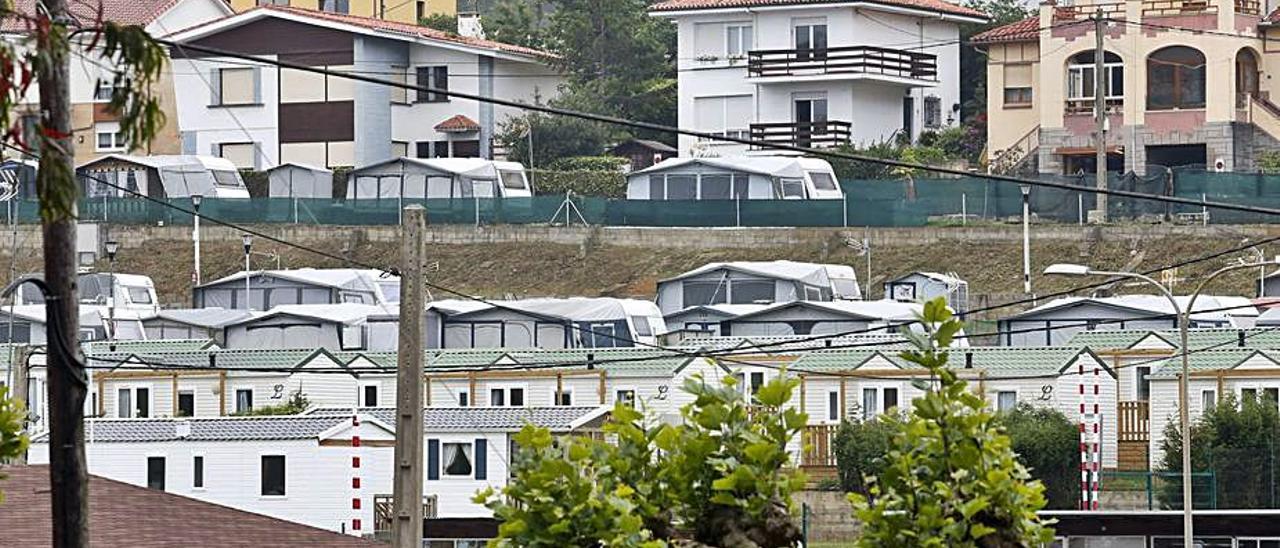 En primer término, los bungalows del camping, con los edificios de La Llada al fondo.