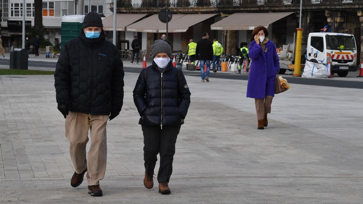 Ciudadanos con mascarilla caminan por el centro de A Coruña.