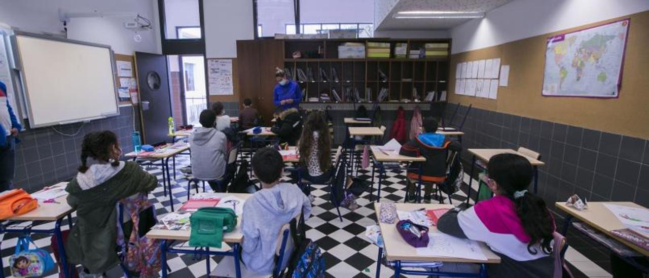 Niñas y niños con mascarilla y separados en el aula de un colegio de Gandia. | ÀLEX OLTRA