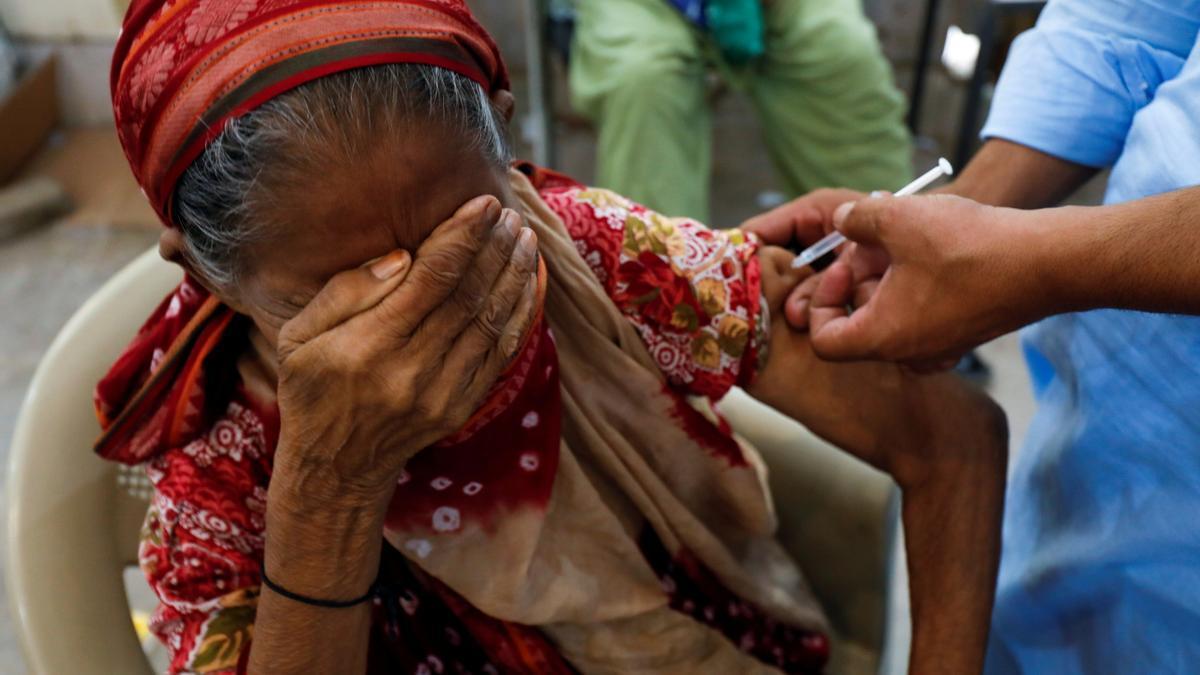 Una mujer pakistaní se tapa los ojos al recibir la vacuna contra el coronavirus.