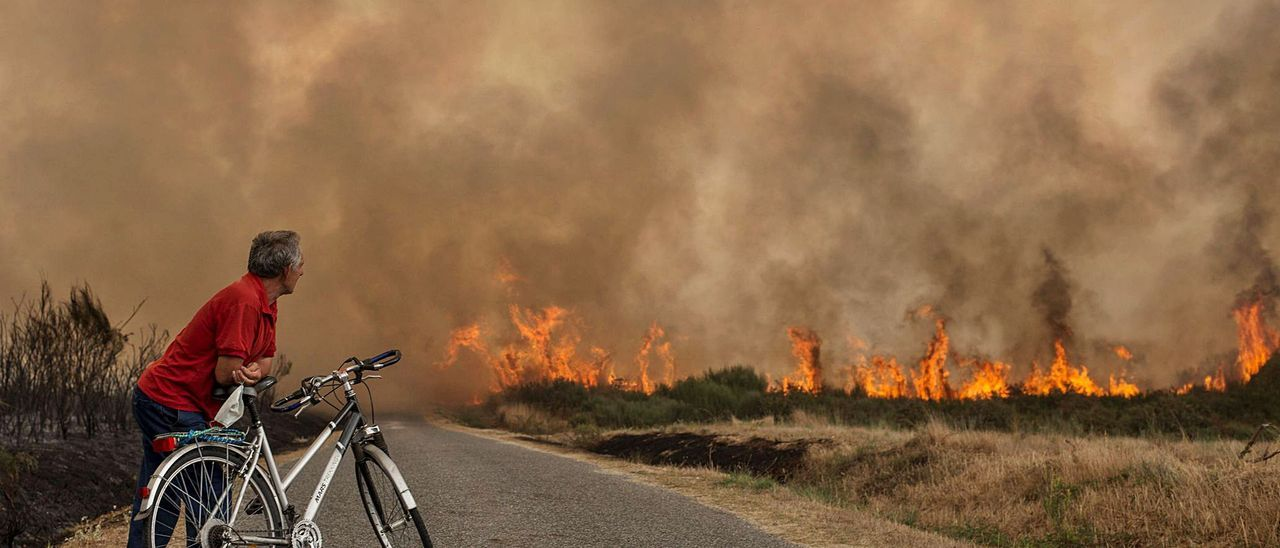 Un vecino  de Cualedro observa el avance de las llamas en un incendio en la localidad.